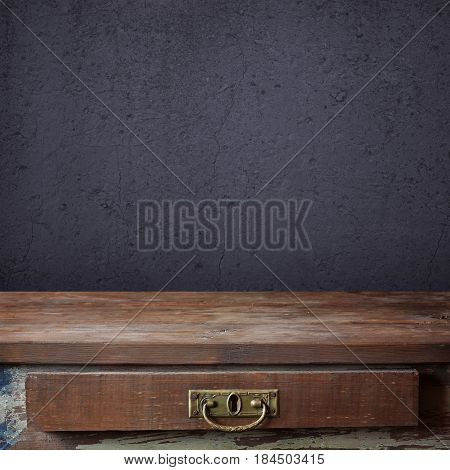 empty wooden table with a drawer on the background of blue wall with cracks. empty space for Your subject.
