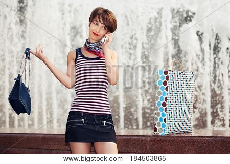 Happy young woman with handbag talking on mobile phone. Stylish fashion model in tank top outdoor