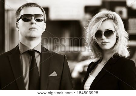 Young business couple walking in city street. Stylish fashion model in sunglasses outdoor