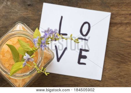 love message card and spa salt aroma of all flowers skin food with purple flowers  on background wood