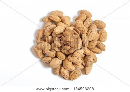 Almonds heart on isolated on white background, almonds in shells in the shape of a heart with some purified nuts on the top, happy valentines day, simplicity