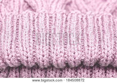 Knitted pattern spokes pink. Knitted cloth background.
