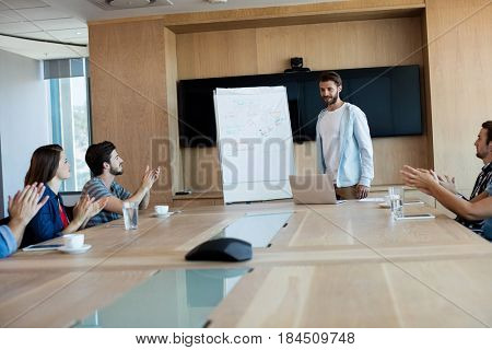 Creative business team applauding while attending a presentation in office