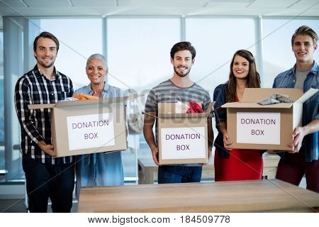 Portrait of creative business team holding donation box in office