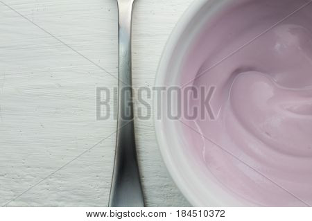 Yogurt close up view form top - Natural rasberry flavored yoghurt in white bowl on white wood table