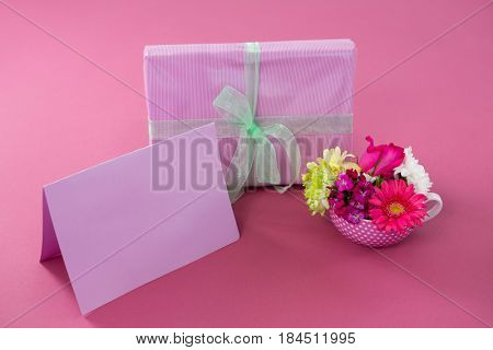 Close-up of gift box with happy mother day tag and blank card against pink background