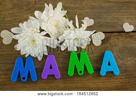 Heart shape with alphabet reading mama and white flowers on wooden plank