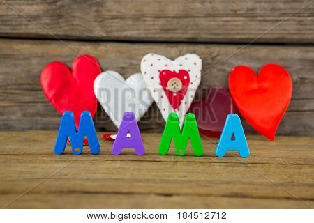 Heart shape with alphabet reading mama on wooden surface