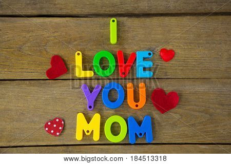 I love you mom message with red hearts on wooden plank