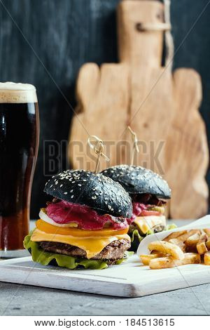 Homemade burger with black bun beef meat and red berries sauce with glass of dark beer and French fries over dark background.