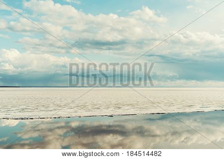 Scenery view of frozen river during ice drift on springtime with dramatic teal sky and clouds having reflections in melt water on evening in Novosibirsk Russia