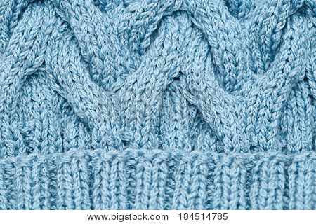 Knitted pattern spokes blue. Knitted cloth background.