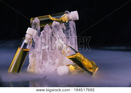 Detail of cannabis oil containers and quartz crystal isolated on black - medical marijuana concept