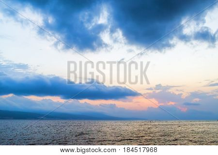 Beautiful morning seascape. Sky with cumulus clouds and a calm sea. Mountains on the horizon. Dawn above the sea.