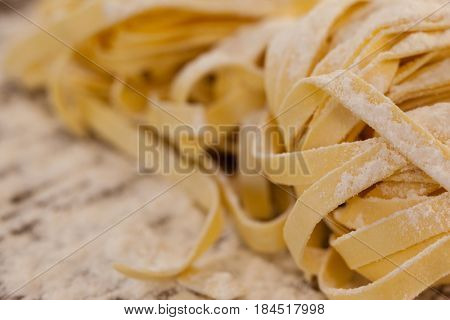 Fettuccine pasta dusted with flour on wooden table