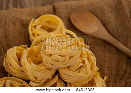 Close-up of fettuccine pasta and wooden spoon on sack