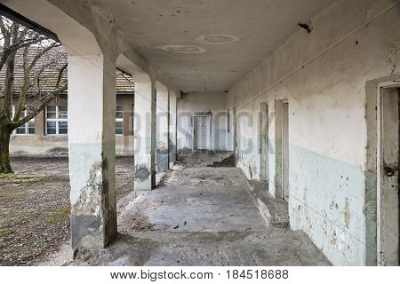 Old abandoned building with pillars and a porch in the village