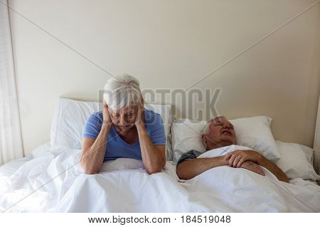 Senior woman getting disturbed with man snoring on bed in bedroom