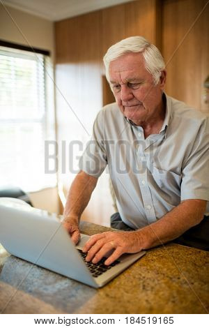 Senior man using laptop in the kitchen at home