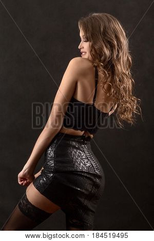 beautiful woman undressing on black background smiling