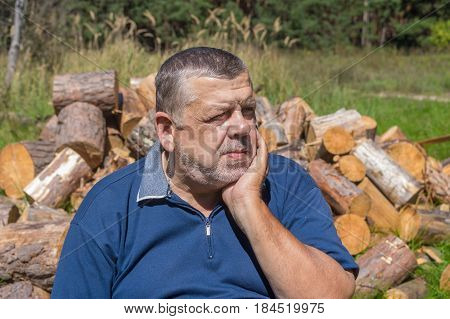 Portrait of elderly Ukrainian peasant ready to chop firewood for house heating in winter