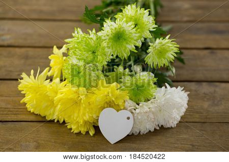 Clos-up of bunch of yellow flowers with heart shape tag on wooden plank