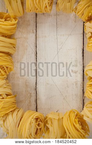 Fettuccine pasta isolated on wooden table