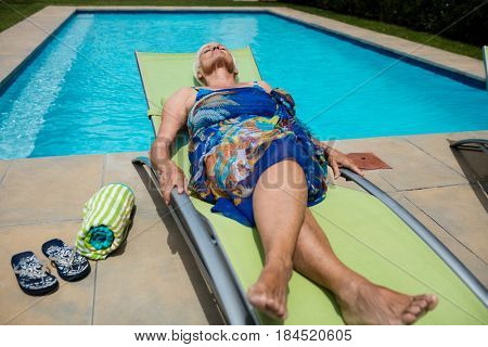 Senior woman sleeping on lounge chair at poolside