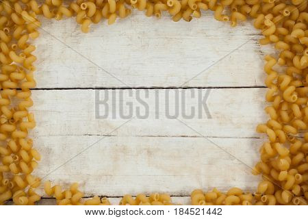 Pipe rigate pasta forming frame on wooden background