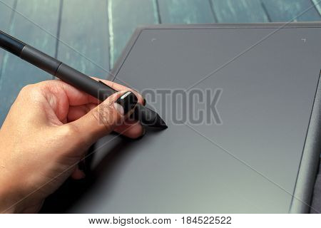 Hand of graphic designer working with stilus and tablet