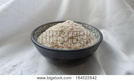 raw and organic Psyllium husk in a bowl with white background