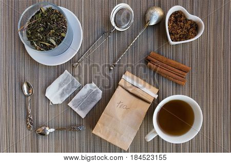 Teatime flat lay. Loose leaf tea in crystal jar tea bags cup of hot tea brown sugar and cinnamon infuser and vintage spoons View from above.