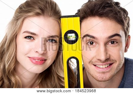 Close-up view of young professional couple with level tool smiling at camera