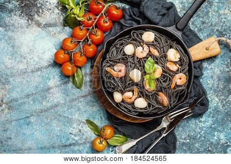 Black spaghetti with prawns and scallop in frying pan on blue background, top view with copy space