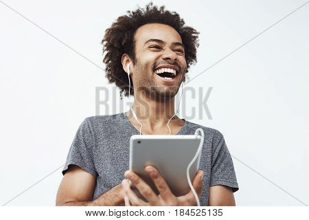 Portrait of cheerful happy african man in headphones laughing holding tablet talking or watching and enjoying a comedy show or browsing over white background.Copy space.
