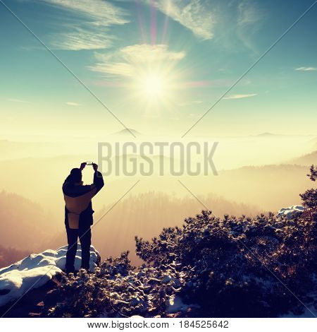 Hiker Hold Phone Above Head, Take Picture Of Misty Winter Landscape