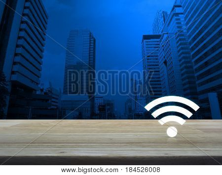 Wi-fi button on wooden table over modern office city tower Technology and internet concept