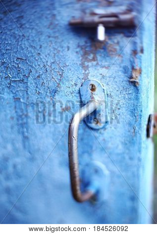 old vintage latch lock on blue shabby cracked painted door close up photo