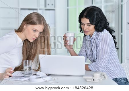 Couple of women are working in the office with a laptop