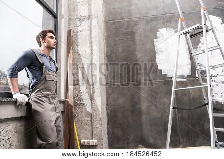 Side View Of Man Resting While Renovating Home, Renovation Home Concept