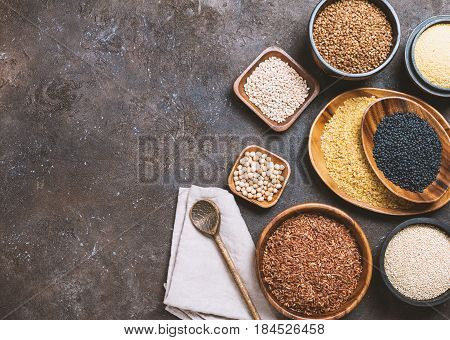 assortment of different cereals and seeds in bowl on dark brown background, top view