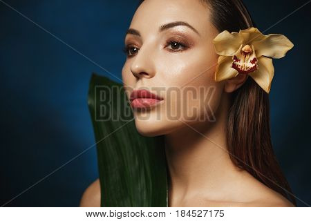 Closeup portrait of woman with slicked back hair, tender flower behind ear. Looking away.