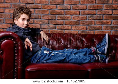 Kid's fashion. Modern nine year old boy posing at studio over brick wall background. Clothes for children.