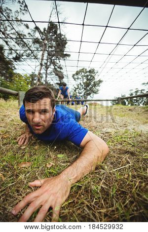 Fit man crawling under the net during obstacle course in bootcamp
