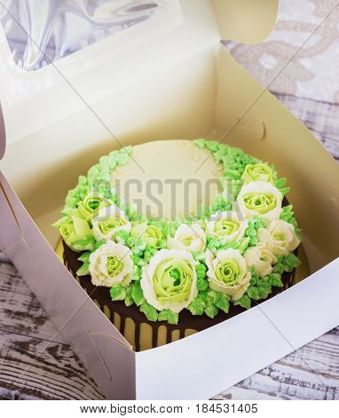 Celebratory cake with roses in the box made of cream on a white wooden background.