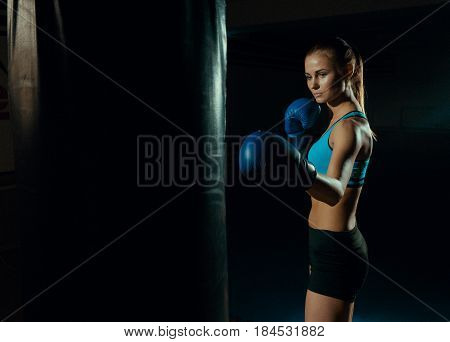 Girl boxer in blue boxing gloves near a punching bag.