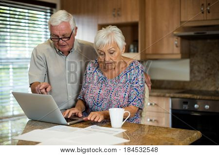 Senior woman using laptop in the kitchen at home