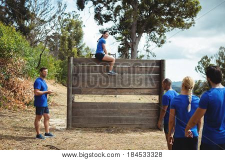 Fit woman sitting over wooden wall during obstacle course in bootcamp