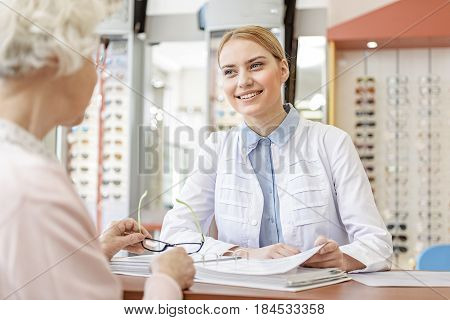 Hilarious female optic store advisor is sitting afore old woman keeping glasses. She looking at her with kind smile. Portrait