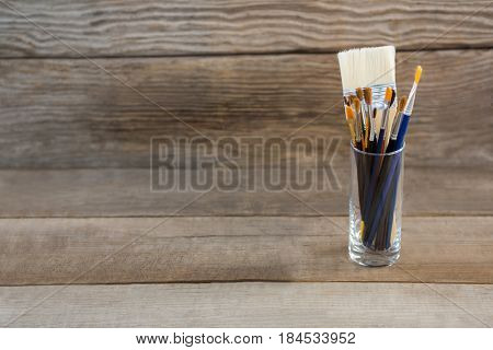 Various paintbrush in a glass container on wood surface